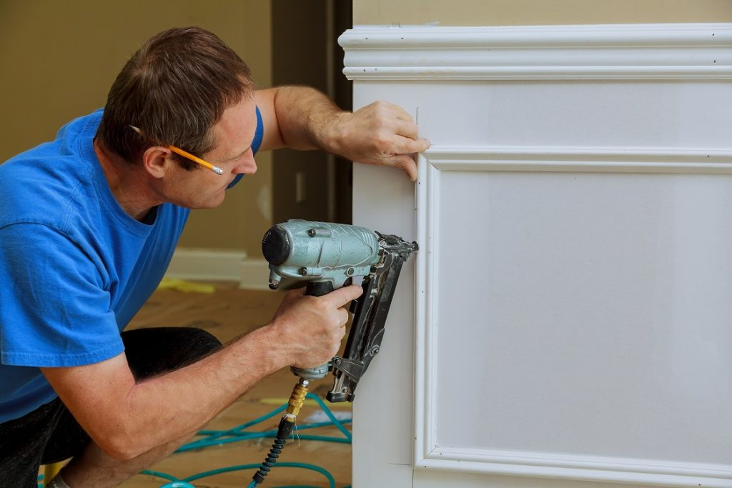 Moulding and millwork technician adding wall highlights to the bottom portion of a wall